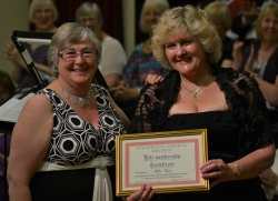 Chairman Caroline Miller presents Helen Pearce with honorary life membership of the choir for her 25 years as secretary